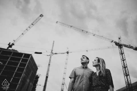 Black and white engagement portrait in DC have this young couple looking to the sky filled with construction cranes