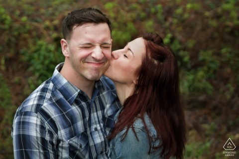 She kisses her fiancé's cheek as he grimaces during their Atlanta Georgia pre-wedding portrait session