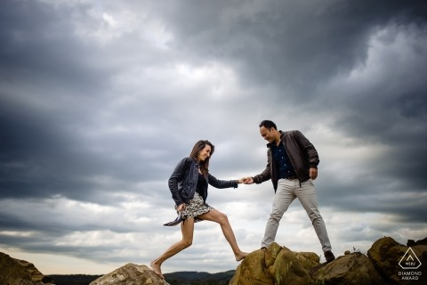 Engagement photography session in Montalcino with a couple hopping across the rocks.