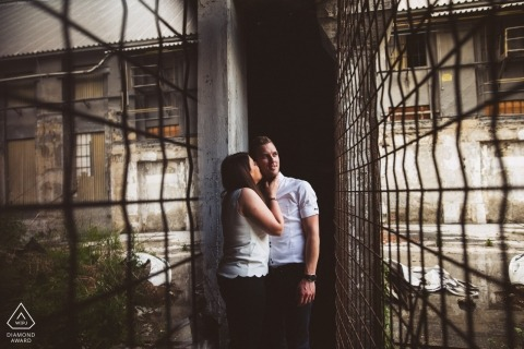 Slovenia pre-wedding portrait session in abandoned and industrial setting with wire mesh fencing