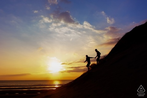 Couple running down the sand dunes on the beach at sunset | England pre-wedding photo shoots