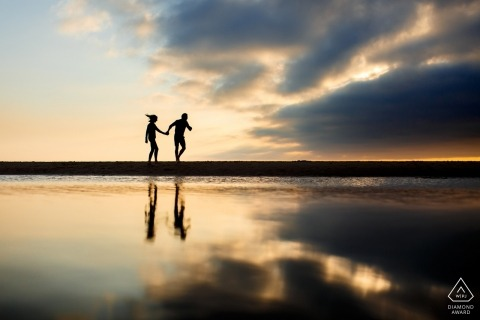 Couple walking across the beach with reflections in the water at sunset | England wedding photography