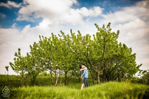 Czech Republic engaged couple kissing near cluster of trees and grassy field