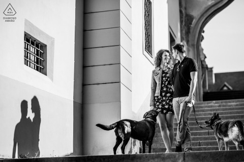Czech Republic couple walk down city stairs with two dogs for their engagement portrait session