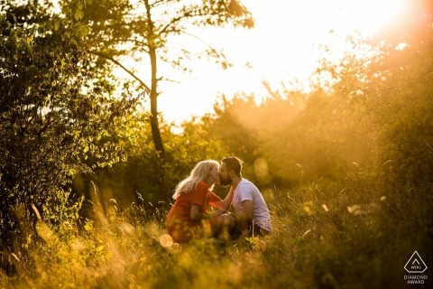 Engagement portrait photo of a couple sitting in a sun drenched grassy field while kissing in the Czech Republic