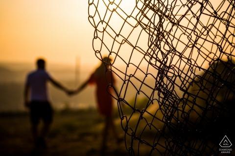 Czech republic sun set engagement portrait shot through old chain link fence