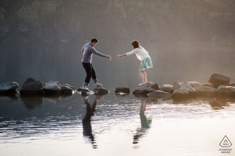Recently engaged Seattle couple reach out to grab each others hand while crossing rocks over water