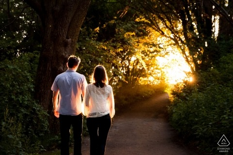 Seattle Washington couple walk hand-in-hand Down a tree cover trail straight into the sun for their engagement portraits