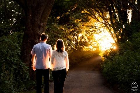 Un couple de Seattle, Washington, marche main dans la main sur un sentier de couvert d'arbres directement au soleil pour leurs portraits de fiançailles