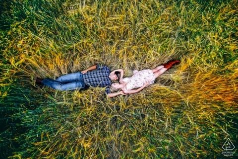 Alberta Engagement Photos of a couple lying in tall grass shot from a drone