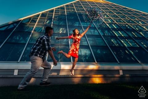 Alberta Engagement Porträt eines Paares in der Sonne mit einem Glasgebäude