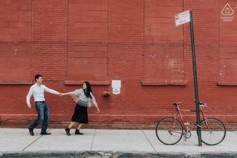 Stedelijk verlovingsportret in Spanje met de handen van een paarholding tegen een rood baksteengebouw met een fiets