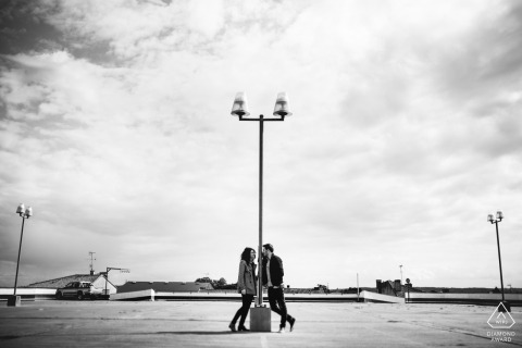 Nouvelle-Aquitaine engaged couple pose near a lap post at an auto park