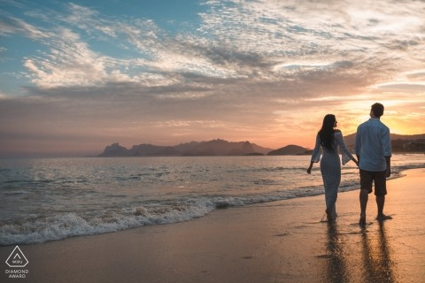 Young lovers take a walk on the beach at sunset in Rio de Janeiro Brazil