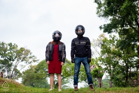 Engagement Photograph of couple wearing motorcycle helmets at the park