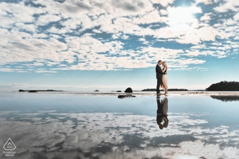 Helsinki Finland pretty wedding portrait with formal dressed couple at water with cloud reflections