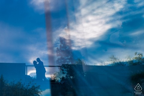 British Columbia Engagement Photo Portraits - window reflection of couple and sky with clouds