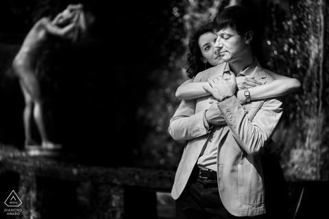 ein verlobtes Paar und eine Statue, die sie beobachtet, Italien, Vittoriale degli Italiani, Gardasee.