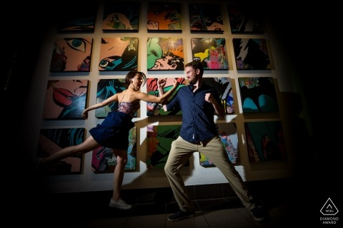 Couple posed in front of comics for engagement portrait | Comic Love in Minnesota