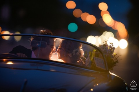 The couple in a vintage car in twilight during their Bangkok engagement session of photography