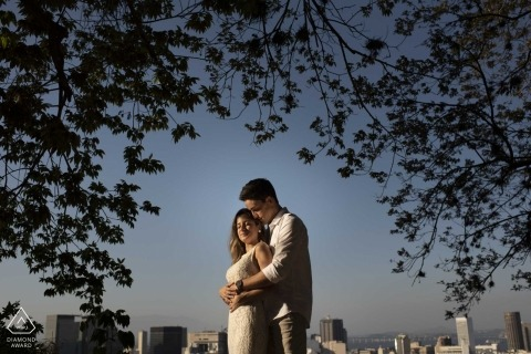 Brazil wedding photographer engagement portrait of a couple in the park with trees and city skyline| Rio de Janeiro pre-wedding pictures
