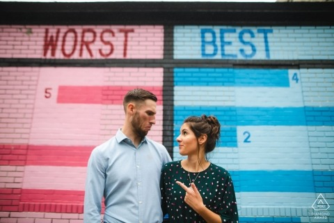 Humorous engagement portrait of a couple with Worst/Best painted wall   Washington DC photographer pre-wedding pictures