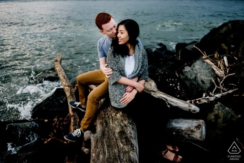 Washington engagement images of a couple sitting on rocks at the ocean | Seattle photographer pre-wedding session