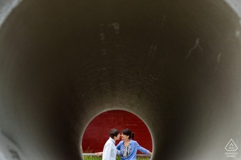 Couple seen through construction pipe - engagement shoot