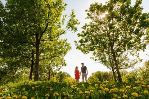Couple marchant sur la colline de pissenlits | Photographe de fiançailles à Montréal