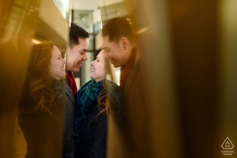 Couple encadré par des reflets dans une sculpture en métal lors de leur séance de fiançailles à Montréal
