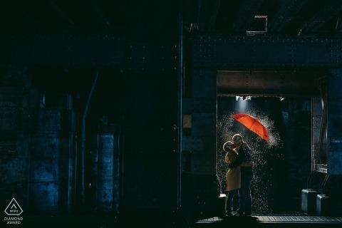 Porträtverpflichtungsphotographie in Madrid im Regen mit rotem Regenschirm nachts