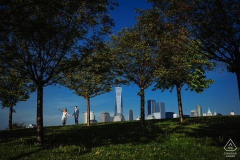 紐約訂婚圖片的一對夫婦在公園與樹木和城市建築| 與攝影師拍婚紗照