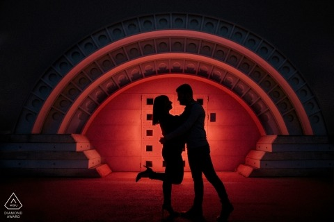 Engagement portrait done in silhouette with red background