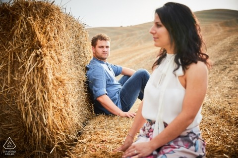 Arezzo pre-wedding engagement pictures of a couple sitting on baled hay in the fields  | Tuscany portrait shoot