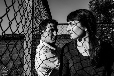 Boston pre - wed image of couple standing near chainlink fence with shadows