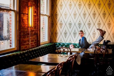 Neu verlobtes Paar in Beucherts Saloon in Washington DC, das während ihrer vorhochzeitlichen Verlobungsporträtsitzung frech ist