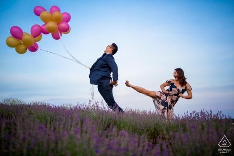"""Frau """"tritt"""" ihrem Verlobten in den Hintern, während er während ihres lustigen und unbeschwerten Verlobungsshootings Luftballons in der Hand hält"""