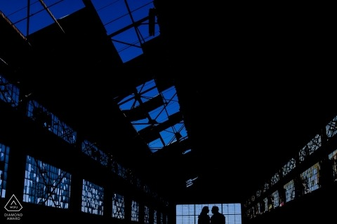 Industrial building engagement pictures of a couple silhouetted | California photographer pre-wedding photo shoot session