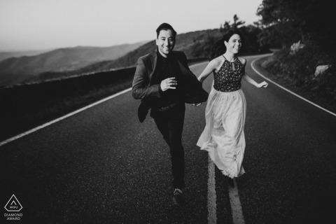 Photos de fiançailles pré-mariage de DC d'un couple courant au milieu d'une route de montagne | séance de portrait sur place