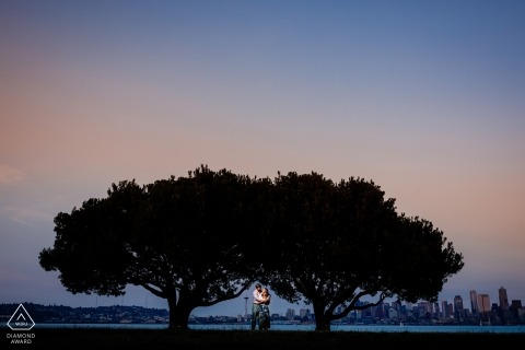 Colorado pre-wedding engagement pictures of a couple with two great trees at dusk | couple photography session