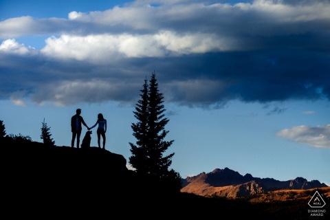 Mountain top engagement pictures of a couple silhouetted   Colorado photographer pre-wedding photo shoot session