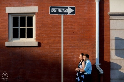 Stedelijke verlovingsfoto's van een paar met bakstenen gebouw en straatnaamborden | Rhode Island fotograaf pre-huwelijksportret sessie