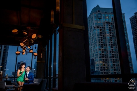 Illinois engagement portraits of a couple indoors at dusk with the city behind them  | Chicago photographer pre-wedding photographer pictures