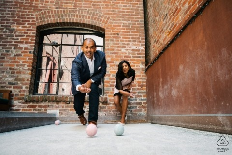 Sacramento pre-wedding engagement pictures of a couple playing Bocce Ball against brick building  | California portrait shoot