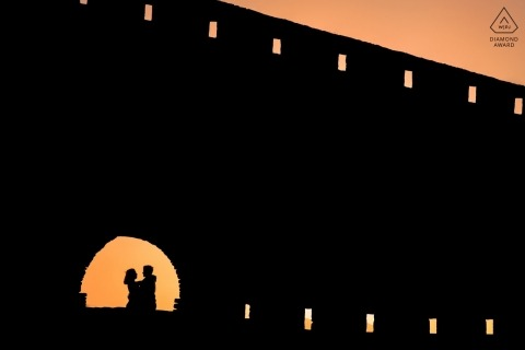 Silhouette engagement portrait of couple hugging in a fortress