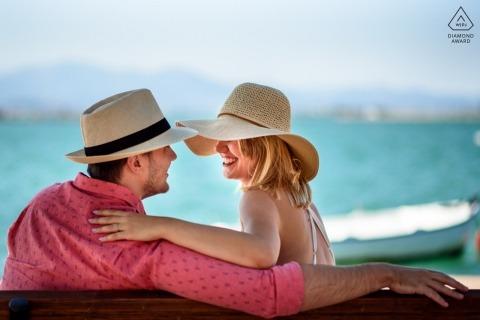 Mädchen, das an ihrem Verlobten mit Sonnenhüten am Strand während des Verlobungsschießens lächelt East Sussex England