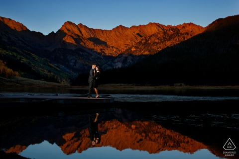 A CO couple poses on the dock as the sun sets on the Gore mountain range during their fall Piney River Ranch engagement in Vail