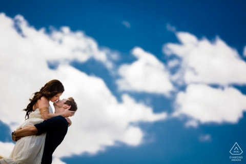 Georgia wedding engagement portrait of a couple kissing below the big blue sky with clouds | Atlanta pre-wedding photographer session