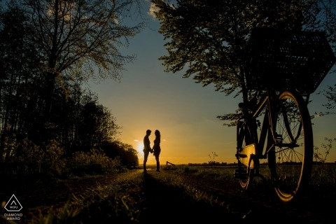 Netherlands engagement pictures of a couple silhouetted with a bike and trees  | The Hagues photographer pre-wedding photo shoot session