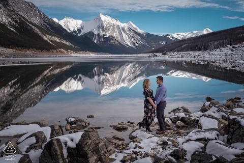 An Alberta engaged couple pose for their pre-wedding portraits at the lake in the mountains for Canadian engagement photographer